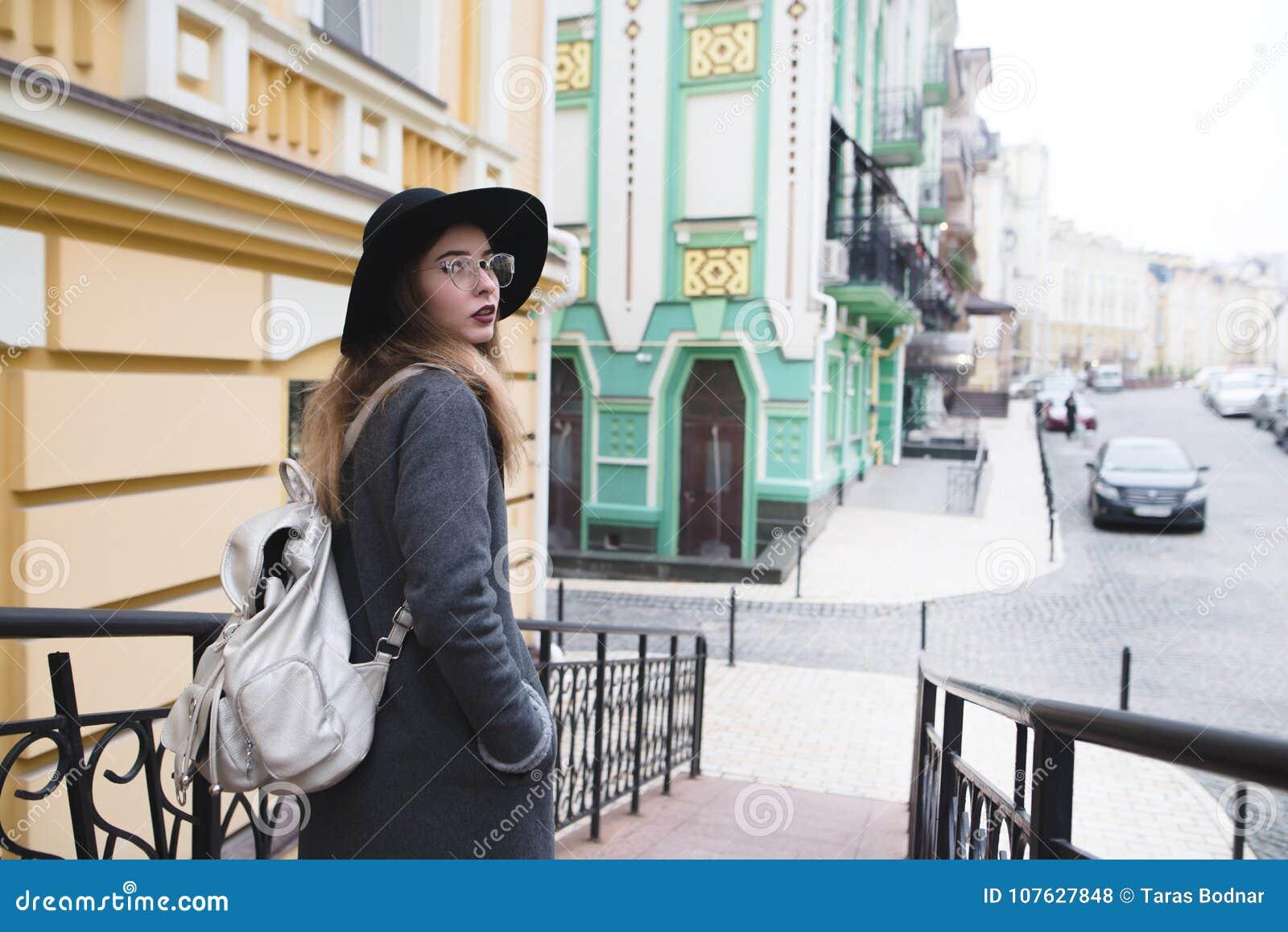Modieus toeristenmeisje die in de mooie oude stad lopen en de camera onderzoeken