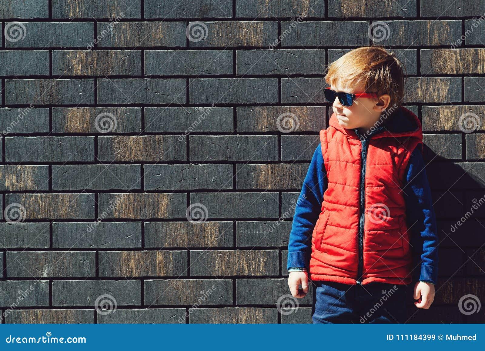Modieus weinig jongen in een modern vest in zonnige dag, in openlucht op bakstenen muurachtergrond