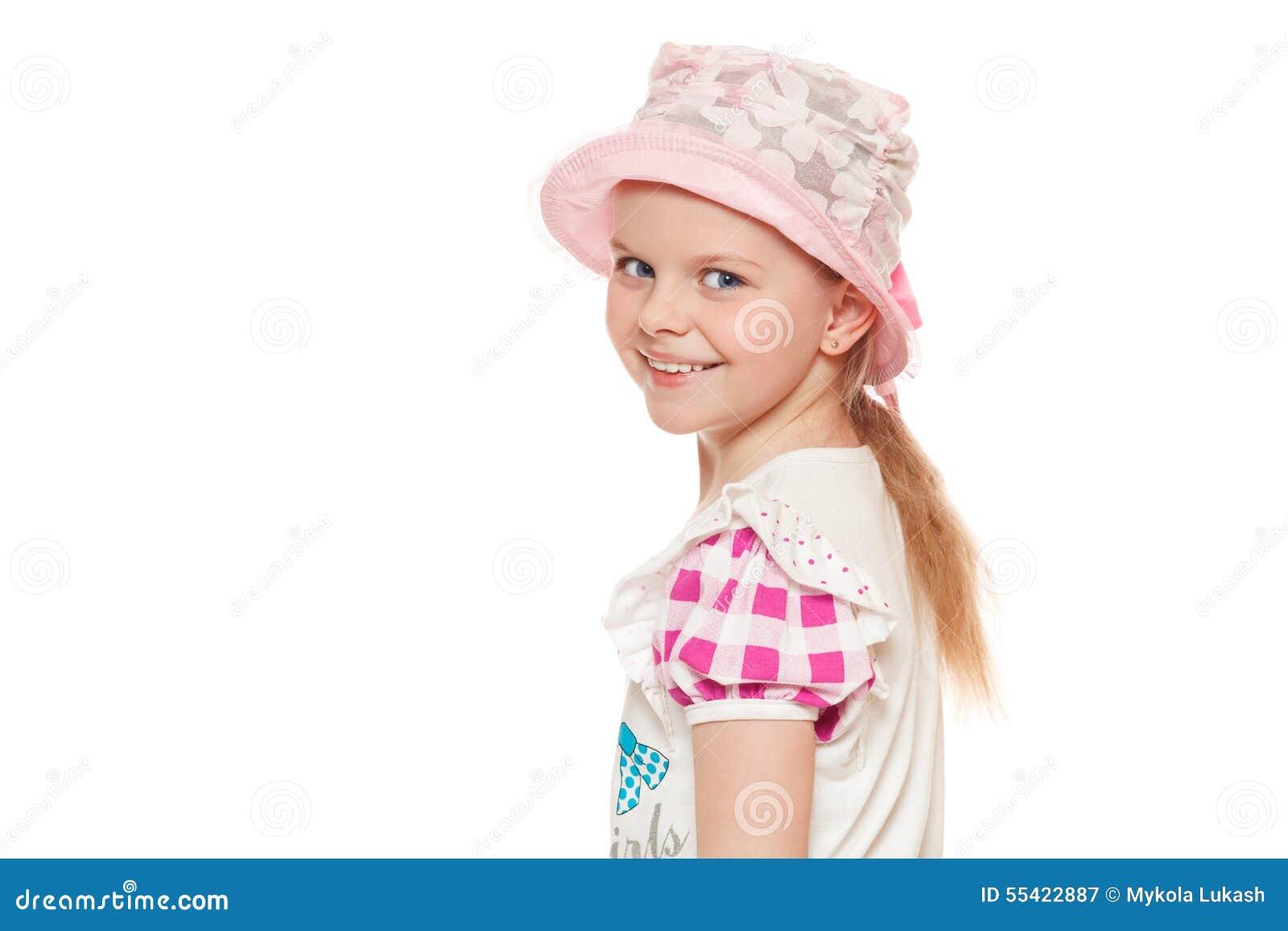 Modieus weinig leuk die meisje in overhemd en hoed, op witte achtergrond wordt geïsoleerd