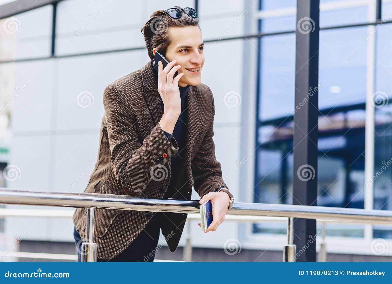 Modieuze aantrekkelijke kerel in jasje met telefoonpaspoort en kaartjes