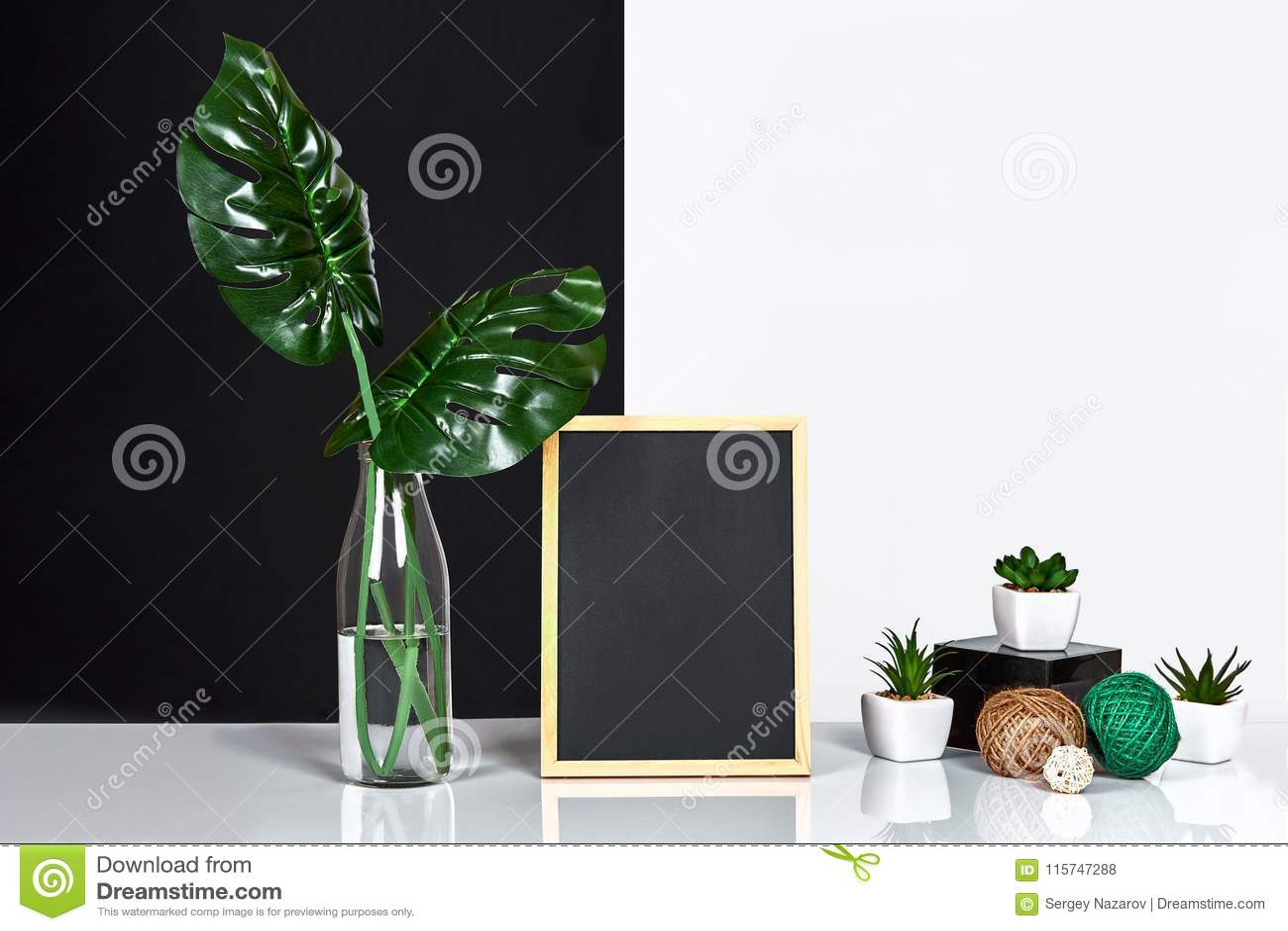 Modieuze binnenlands met spot op affichekader, bladeren in glasfles op lijst met zwart-witte muur op achtergrond