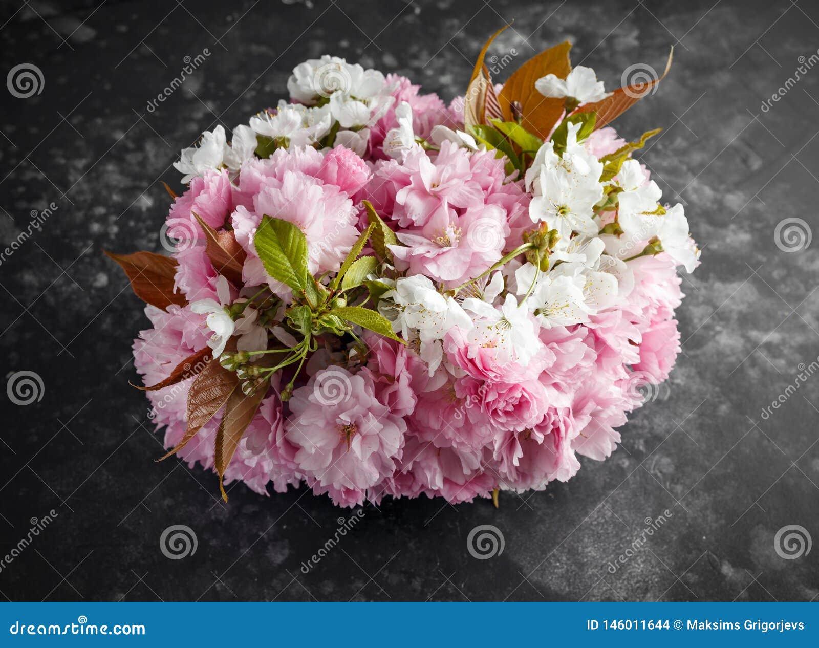 Modieuze bruids bouqet van tedere witte en roze sakurabloemen