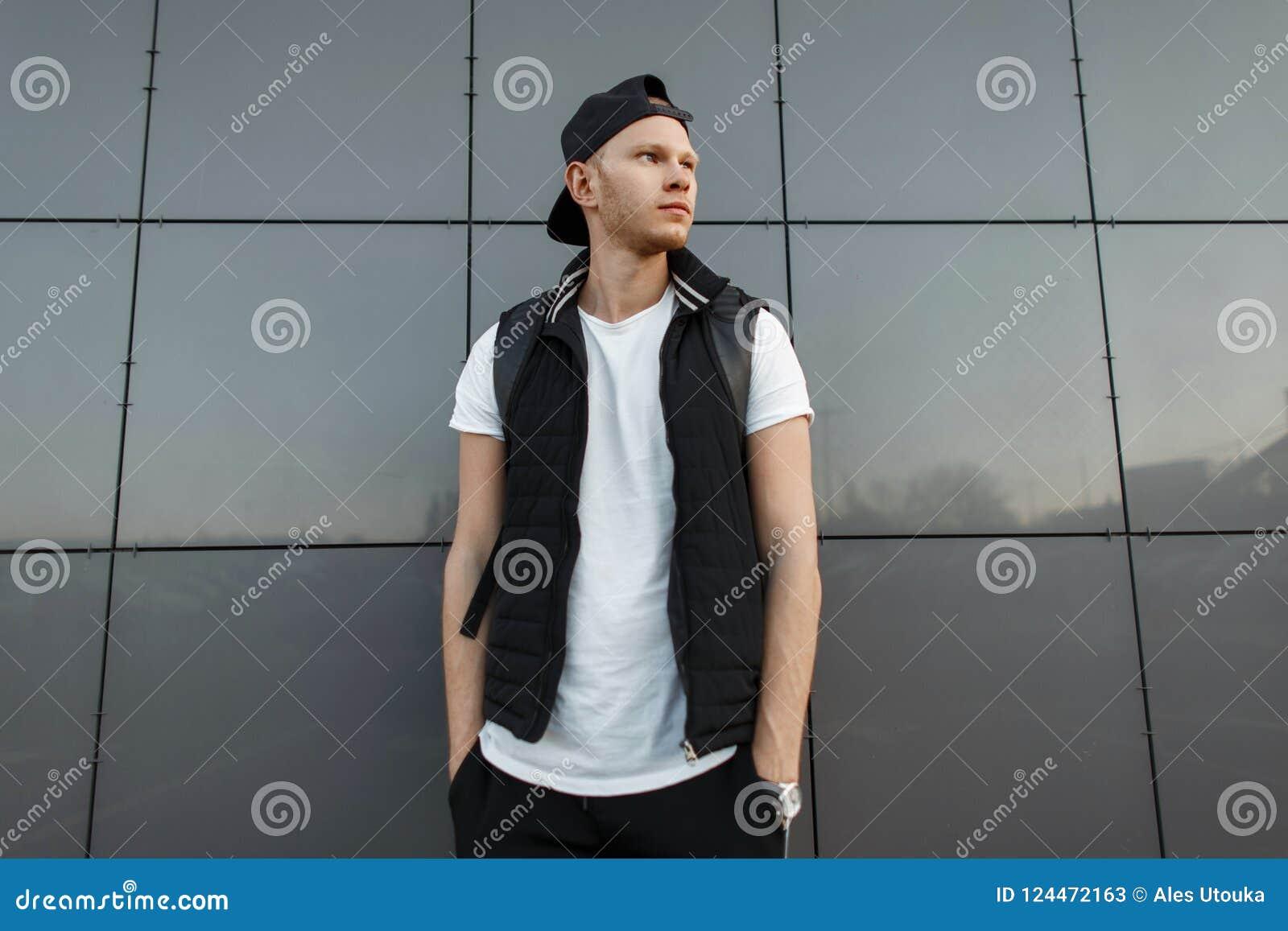 Modieuze jonge mens in een zwart GLB en een zwart modieus vest