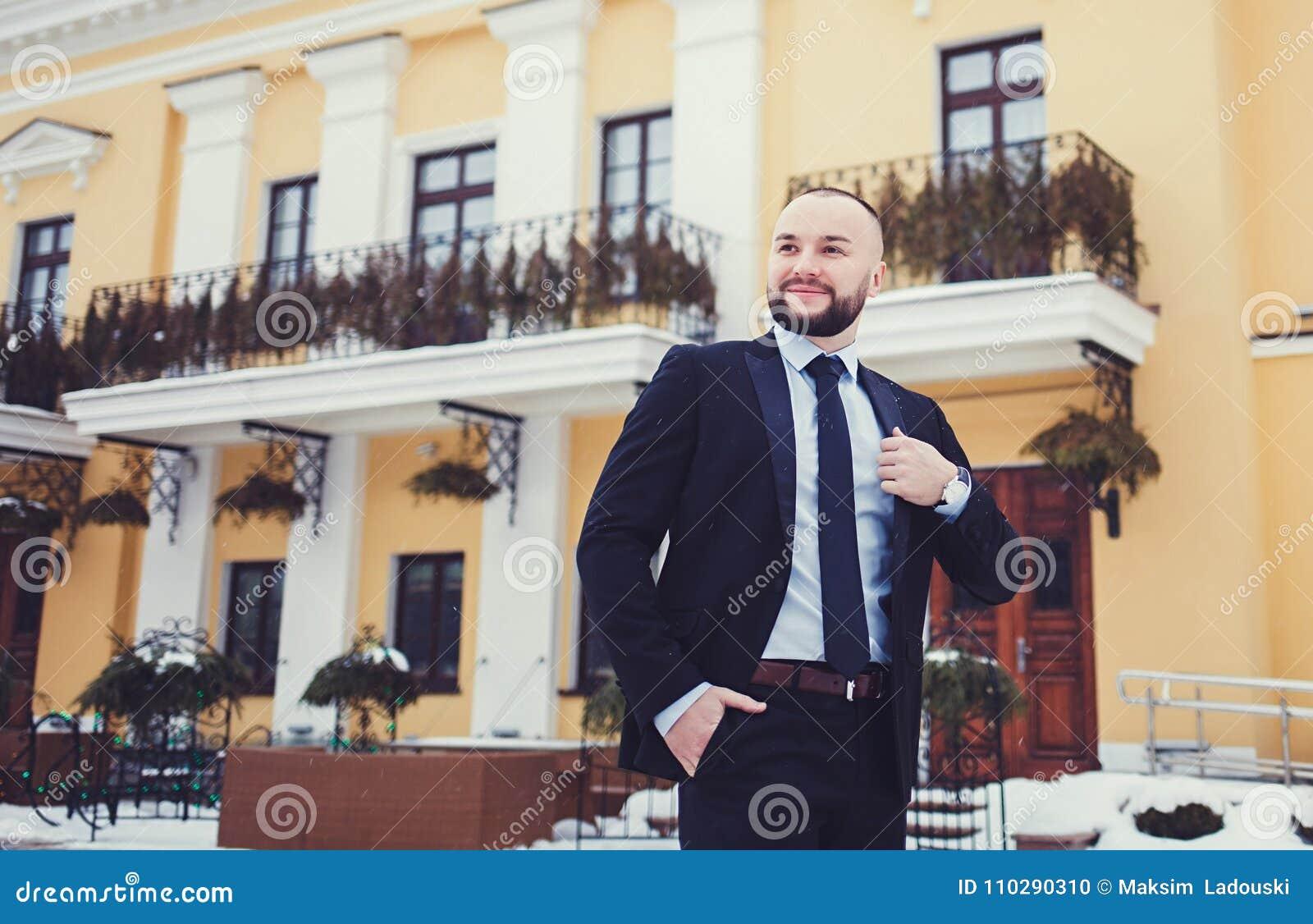 Modieuze jonge mens in kostuum en band