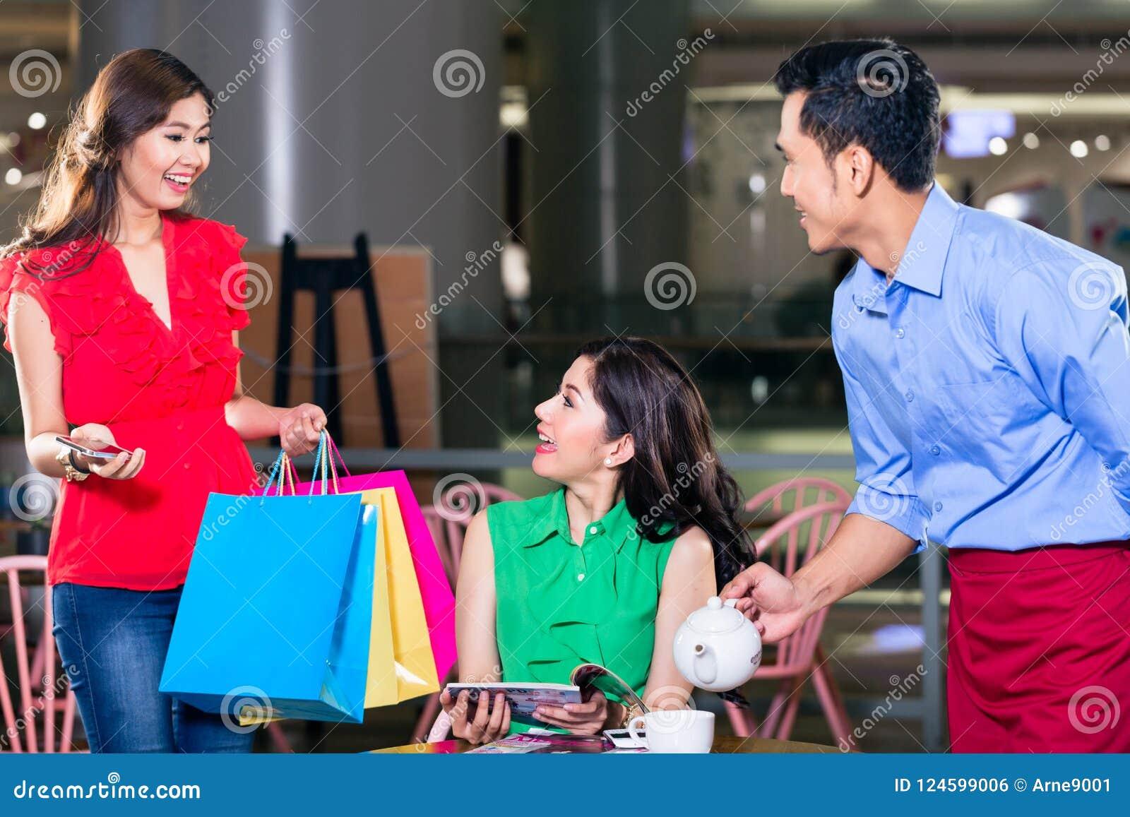 Modieuze jonge vrouw die gelukkig voor het ontmoeten van een vriend in een koffiewinkel kijken