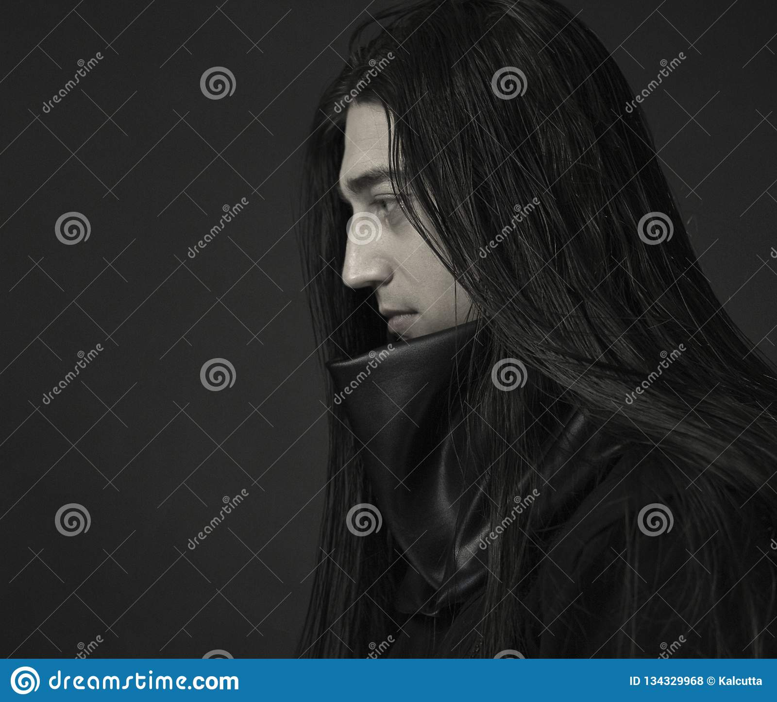 Modieuze knappe jonge mens Kaukasisch man portret mens in zwarte kleren met donker lang haar