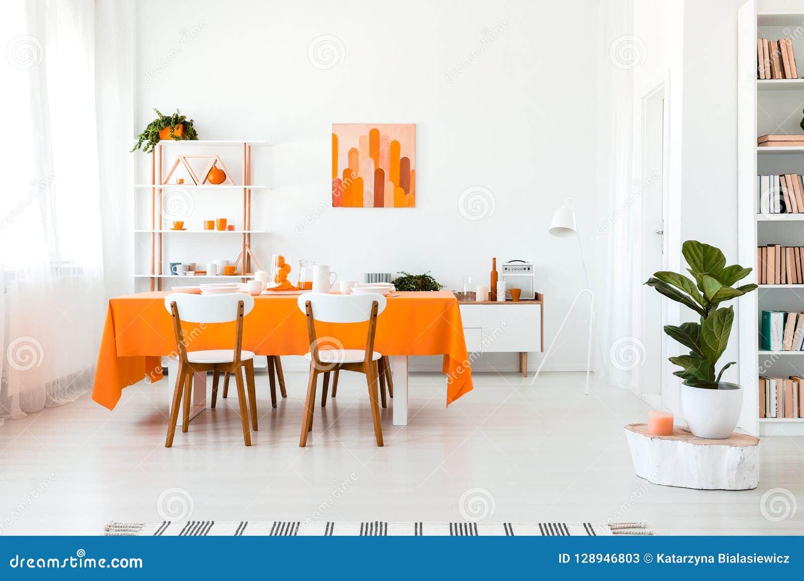 Modieuze maar eenvoudige eetkamer in levendige kleur Oranje en wit binnenlands ontwerpconcept