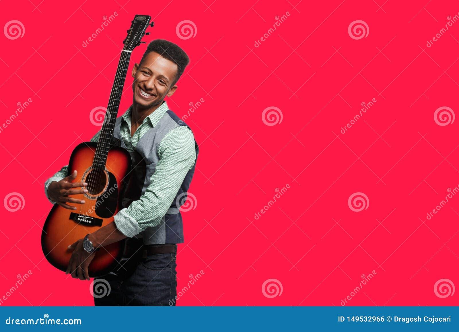 Modieuze mens met gitaar in studio De jongelui die hipster bemant het stellen met gitaar in zijn wapens op rode achtergrond gliml