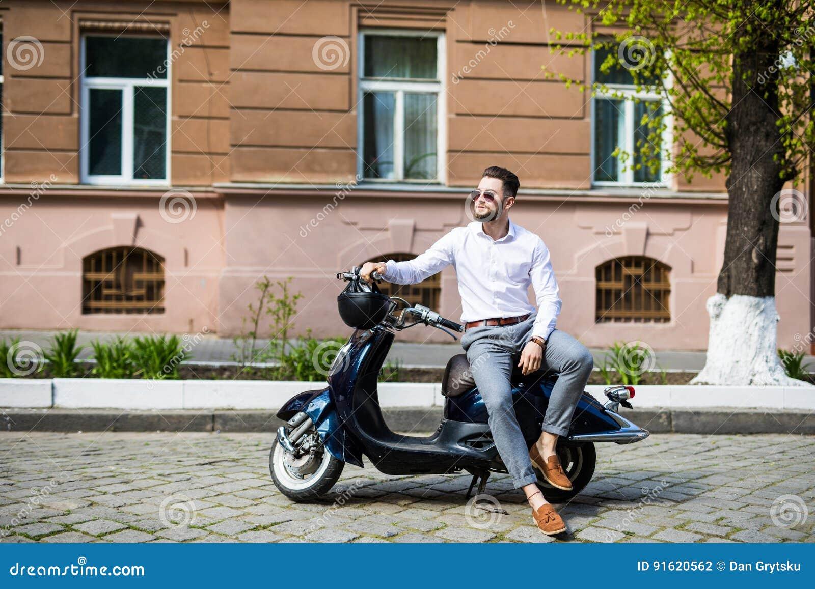 Modieuze in mens moderne zonnebril dragen en een formele kostuumzitting die op een motorfiets op stadsstraat wachten