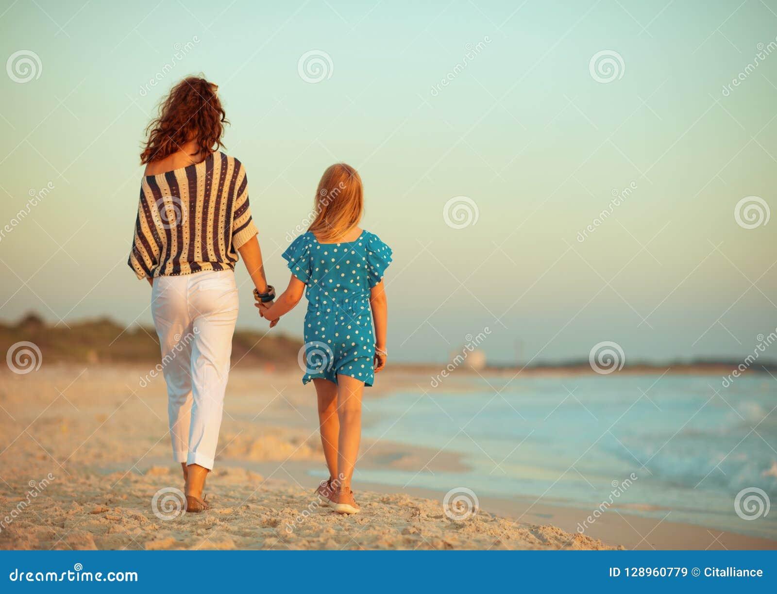 Modieuze moeder en dochter op zeekust in avond het lopen