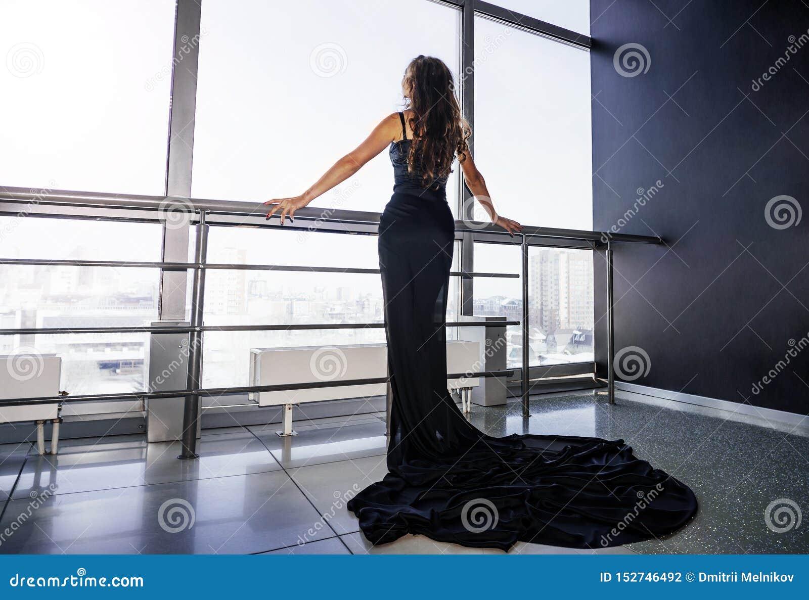Modieuze mooie jonge donkerbruine vrouw dichtbij een venster, in zwarte kleding Samenkomende nieuwe dag, die van de ochtend op va