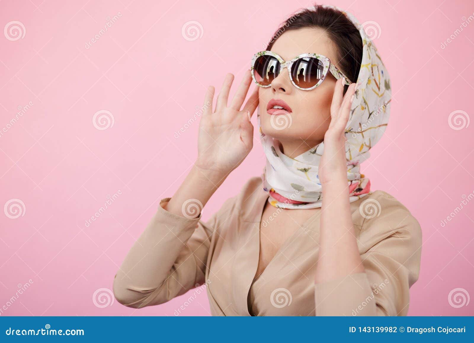 Modieuze zekere donkerbruine vrouw wat betreft zijn zonnebril, die in sjaals dragen, die geïsoleerd op een roze achtergrond omhoo