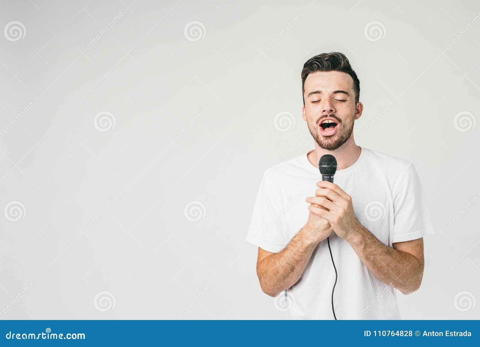 Modigt grabbanseende på den vita väggen och innehavet en mikrofon med hans båda händer Han sjunger sinnlig och ledsen sång med
