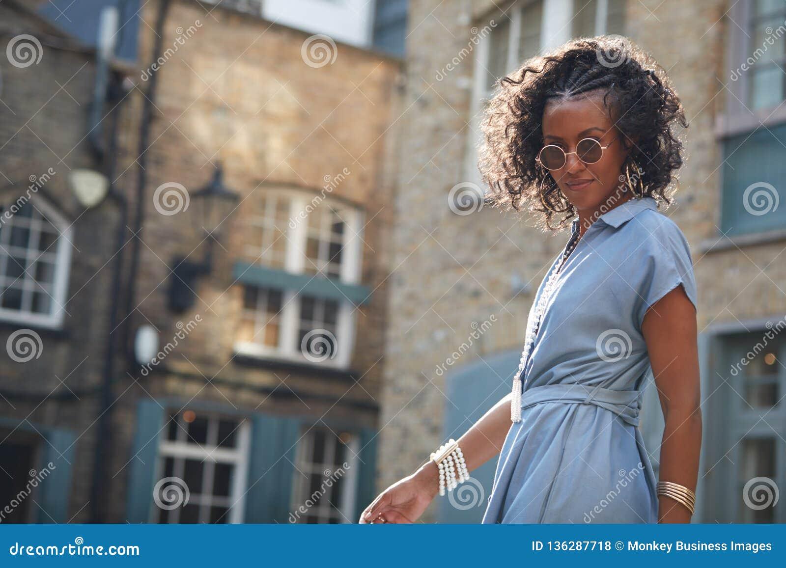 Modische Frau im blauem mit einer Kappe bedecktem Ärmelkleid und -Sonnenbrille