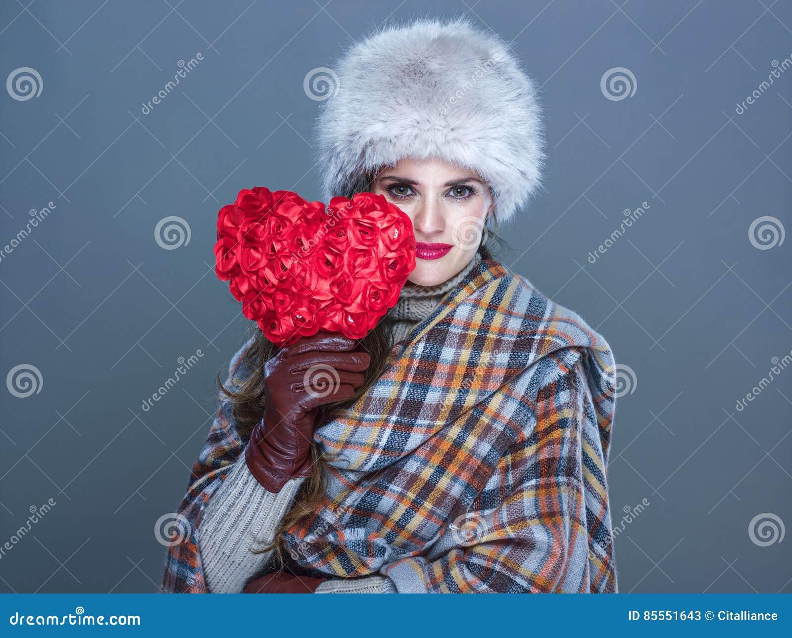 Modische Frau lokalisiert auf kaltem blauem Hintergrund mit rotem Herzen