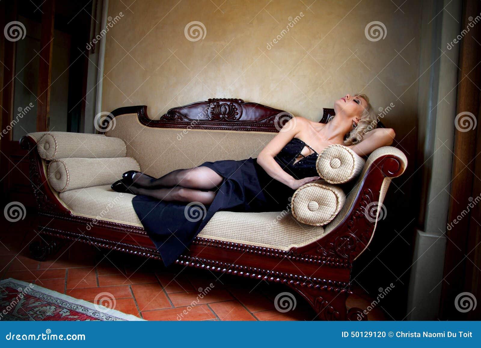 mod le de charme avec la robe de soir e noire se trouvant sur un divan victorien moderne photo. Black Bedroom Furniture Sets. Home Design Ideas