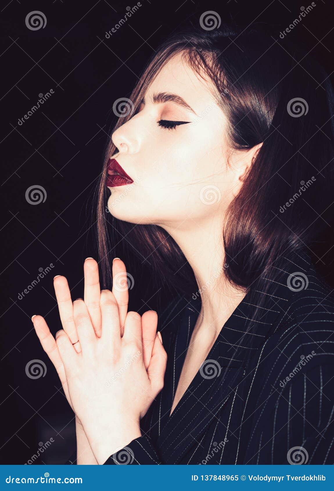 Modli się pojęcie i mieć_nadzieja Dziewczyna na spokojnej twarzy z zamkniętymi oczami w czarnej kurtce, czarny tło elegancka make