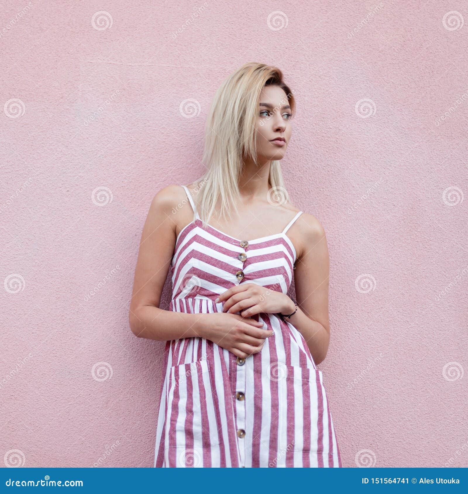 Modna ładna młodej kobiety blondynka w modnych menchiach paskował smokingowy pozować blisko różowej rocznik ściany na ulicie w mi