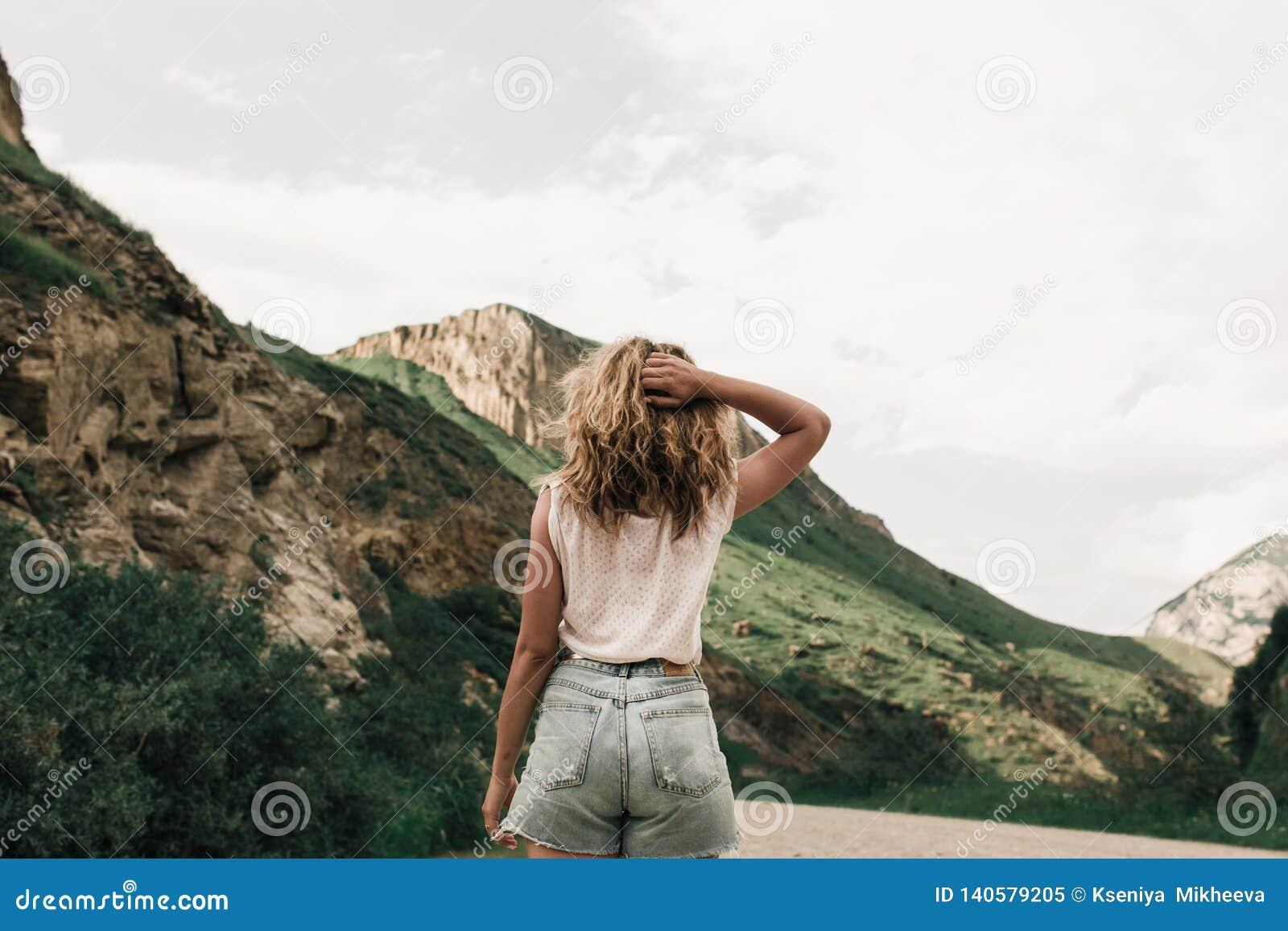 Modna dziewczyna stoi na drodze w średniogórzach w biel ubraniach Zielona trawa i góry
