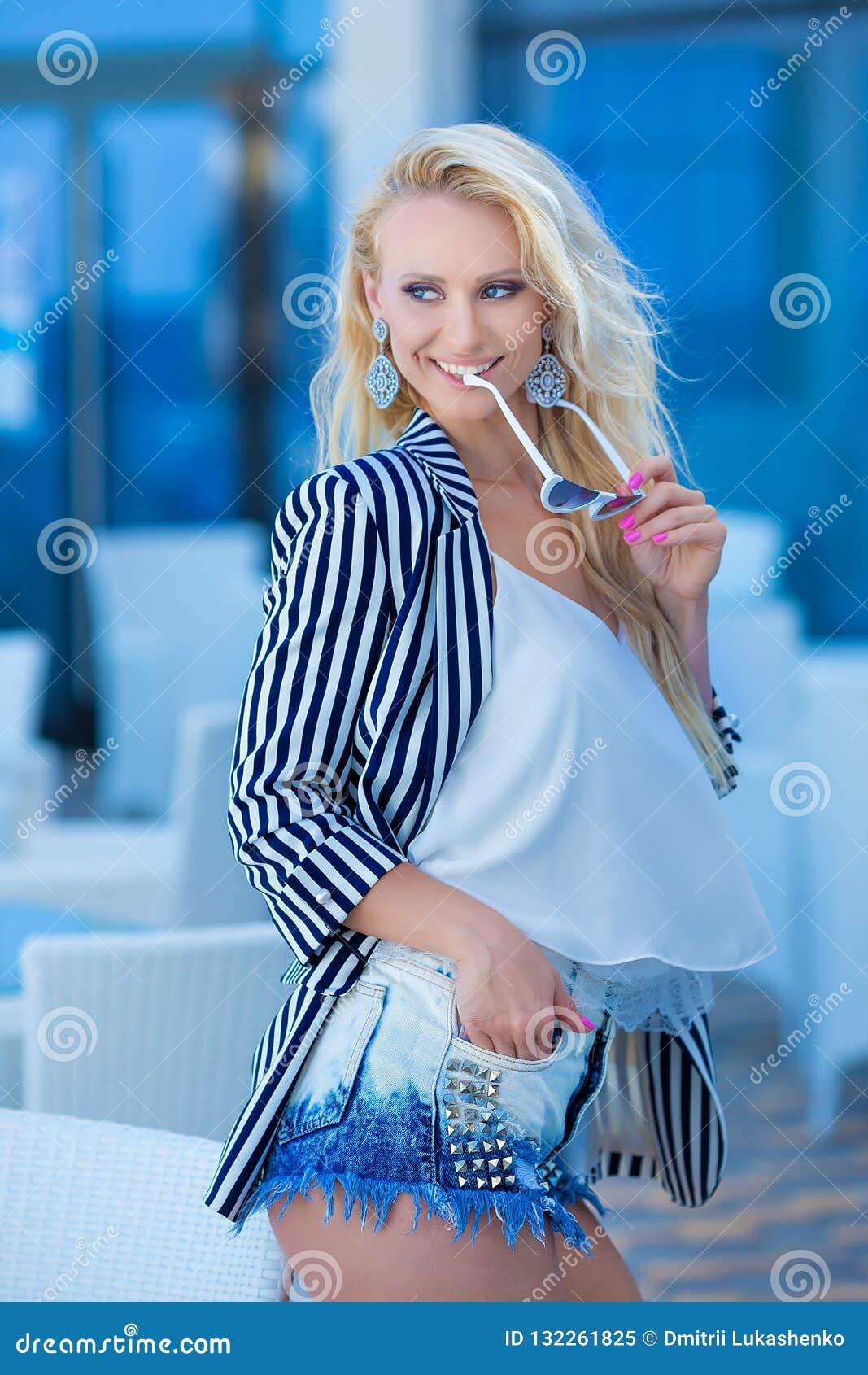 Modna fotografia wspaniała młoda dama z blond kędzierzawym włosy i jaskrawym makeup w eleganckiej nowożytnej sukni cajgi i cukier