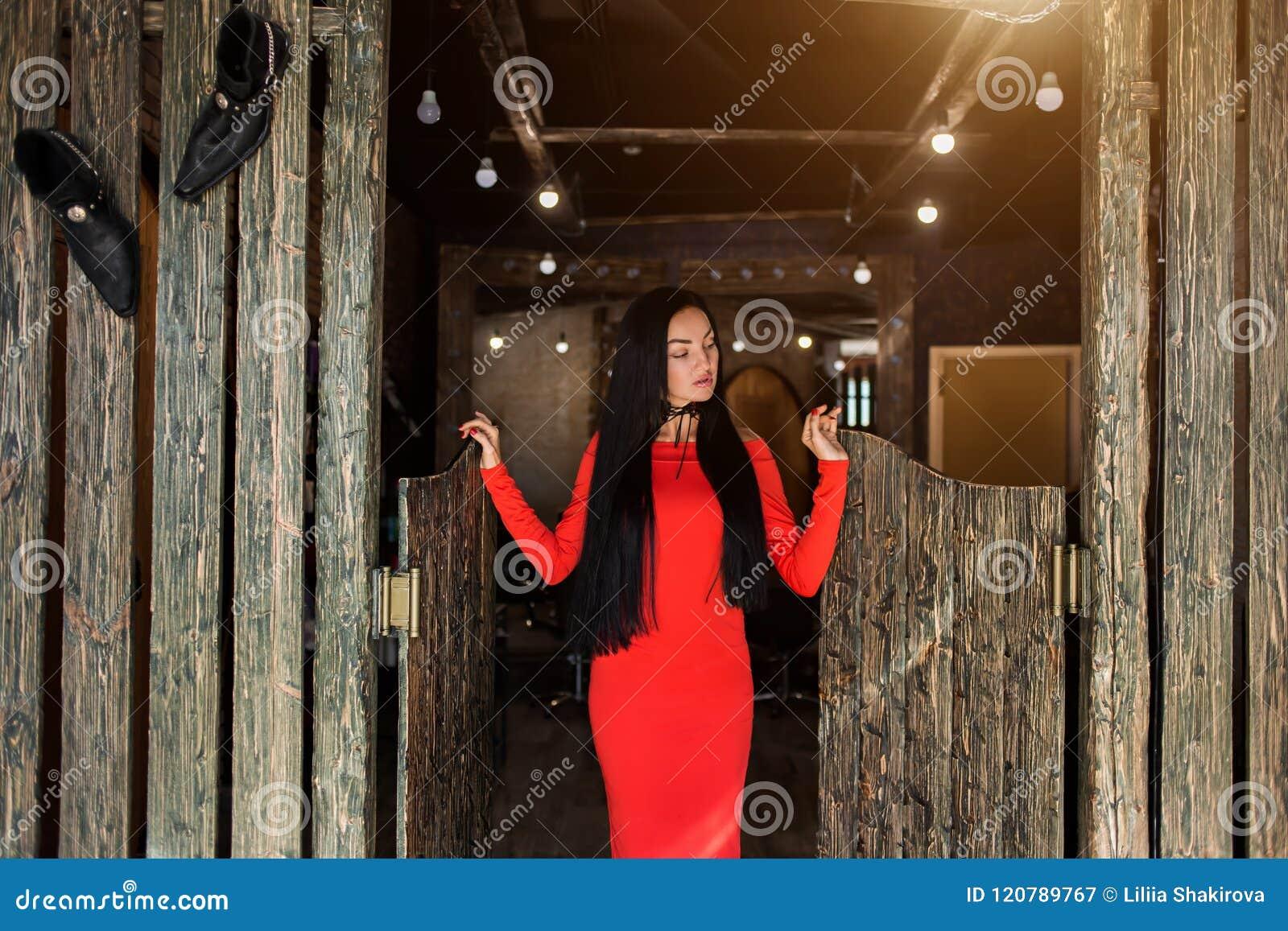 Modna młoda kobieta z długim brunetka włosy w czerwieni sukni i stoi i spojrzenia zestrzelają