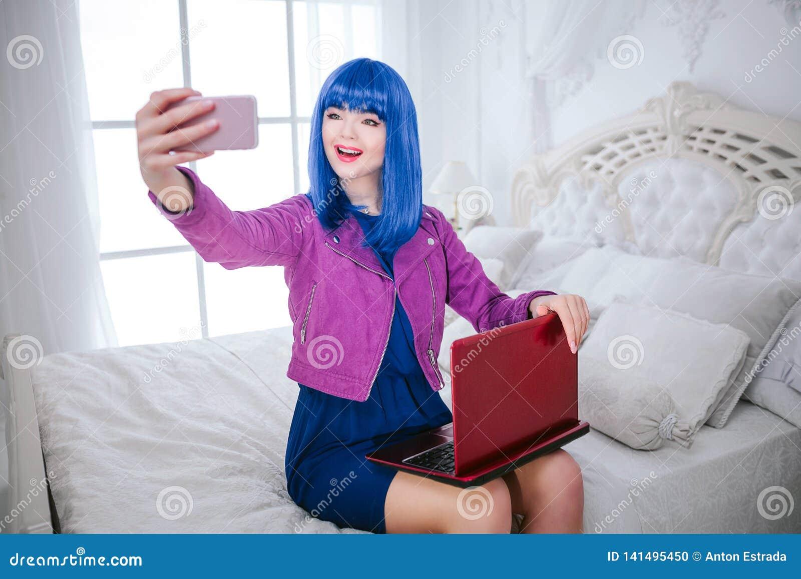 Modna pokraka Splendor uśmiechnięta piękna kobieta z błękitnym włosy i modnym makeup trzyma komputerowy i robi selfie
