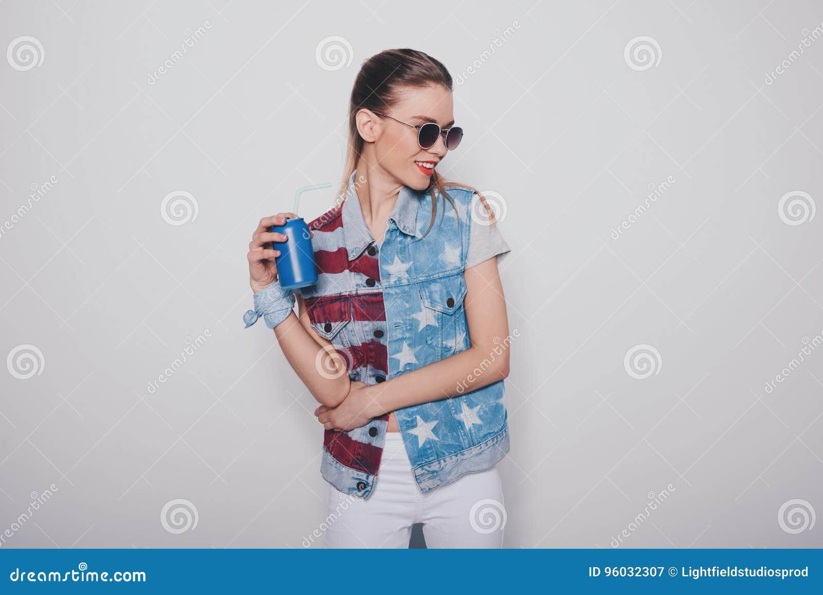 Modniś blondynki dziewczyna trzyma sodowaną puszkę odizolowywająca na popielatym w amerykańskim patriotycznym stroju i okularach