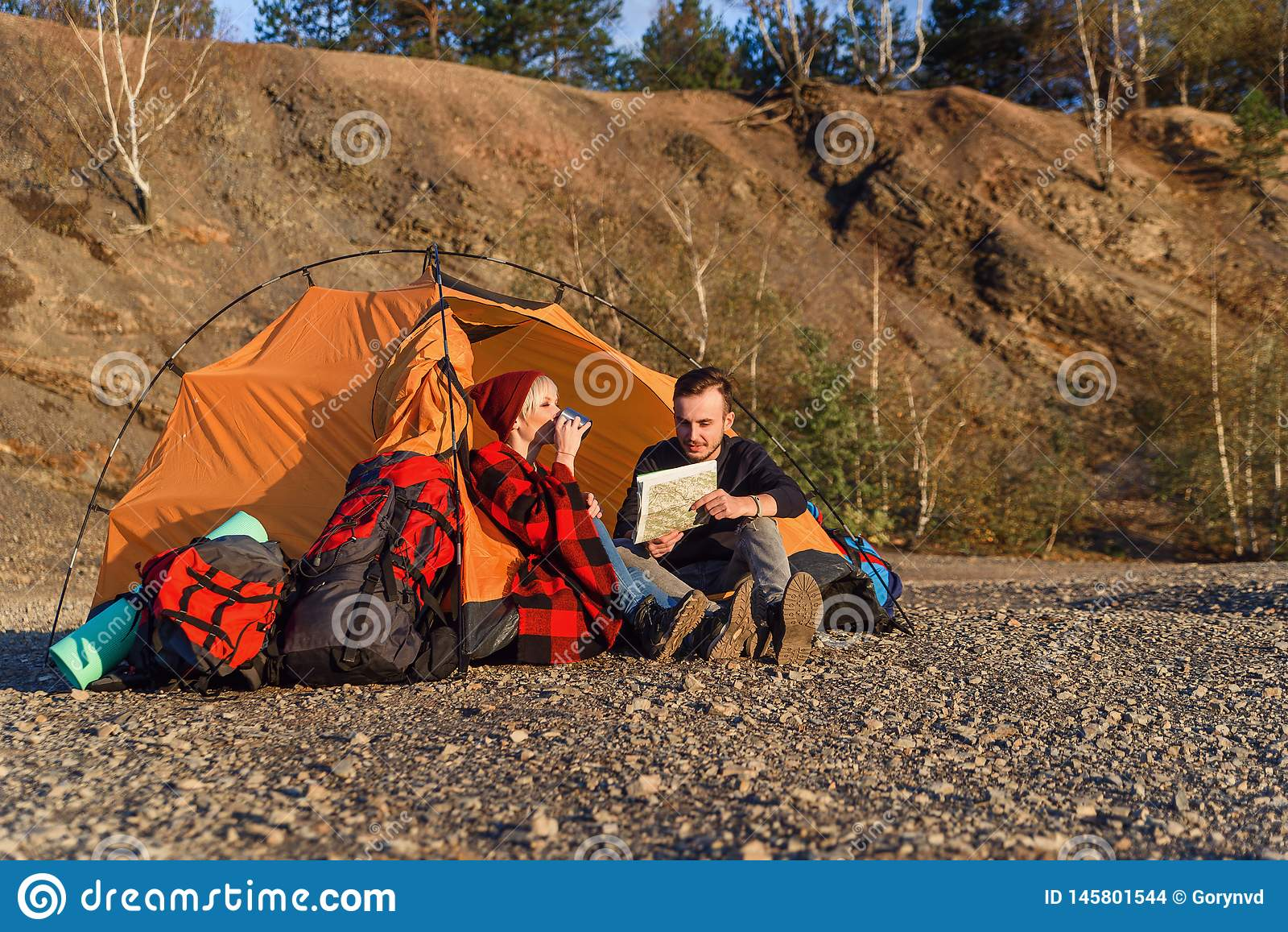 Modniś caucasian uroczej pary rekonesansowa mapa, napoje i podczas gdy siedzą w