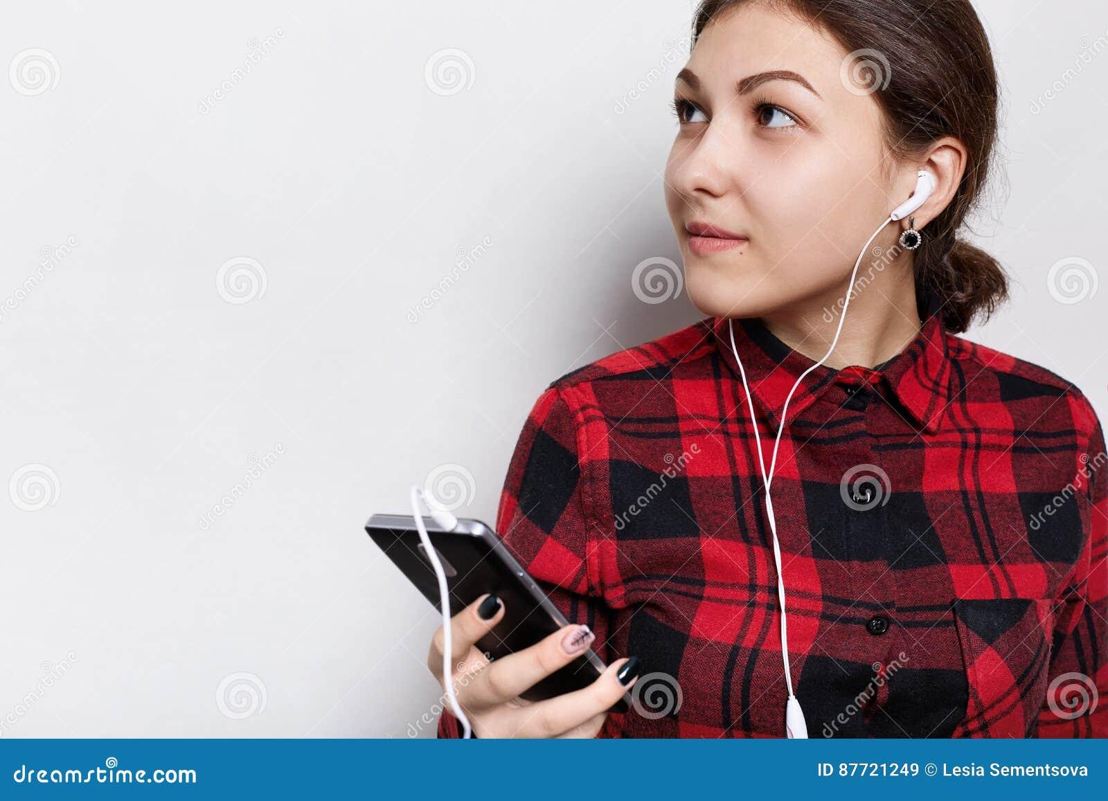 Modniś dziewczyna słucha muzyka lub audiobook w czerwieni sprawdzał koszula ma włosy splatającego w ogonu mienia telefonie komórk