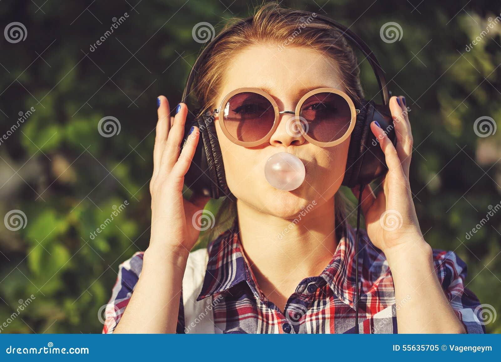 Modniś dziewczyna słucha muzyka na hełmofonach i żuć cud