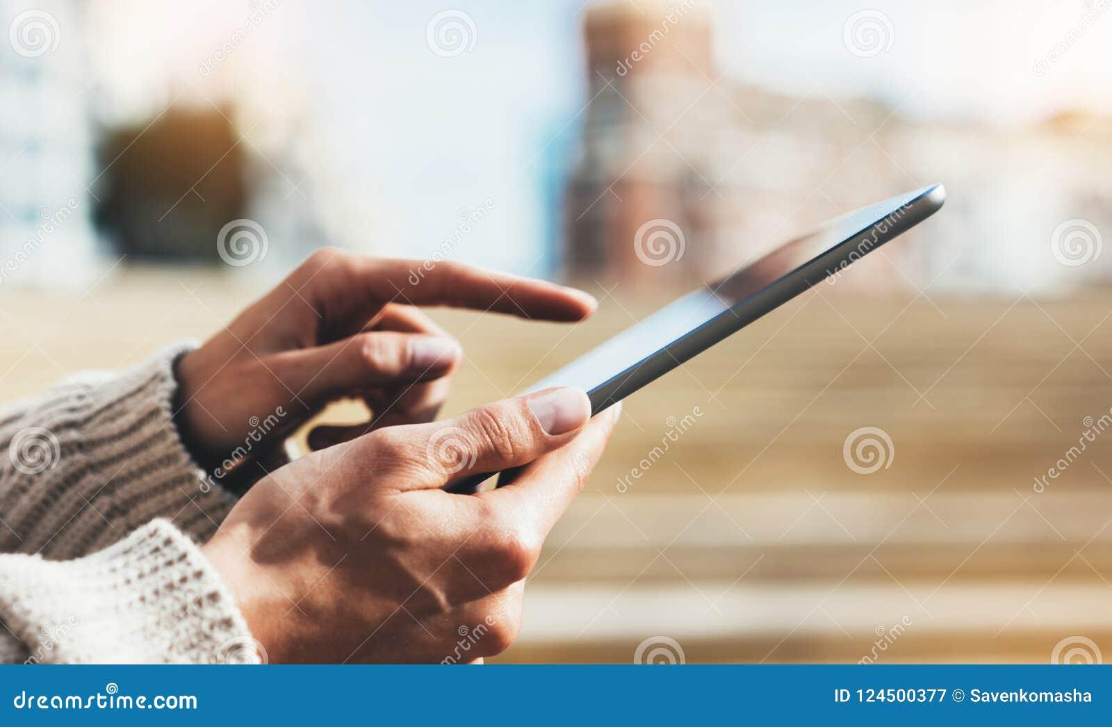 Modniś dziewczyna używa pastylki technologii internet, blogger osoby mienia komputer na tła słońca mieście