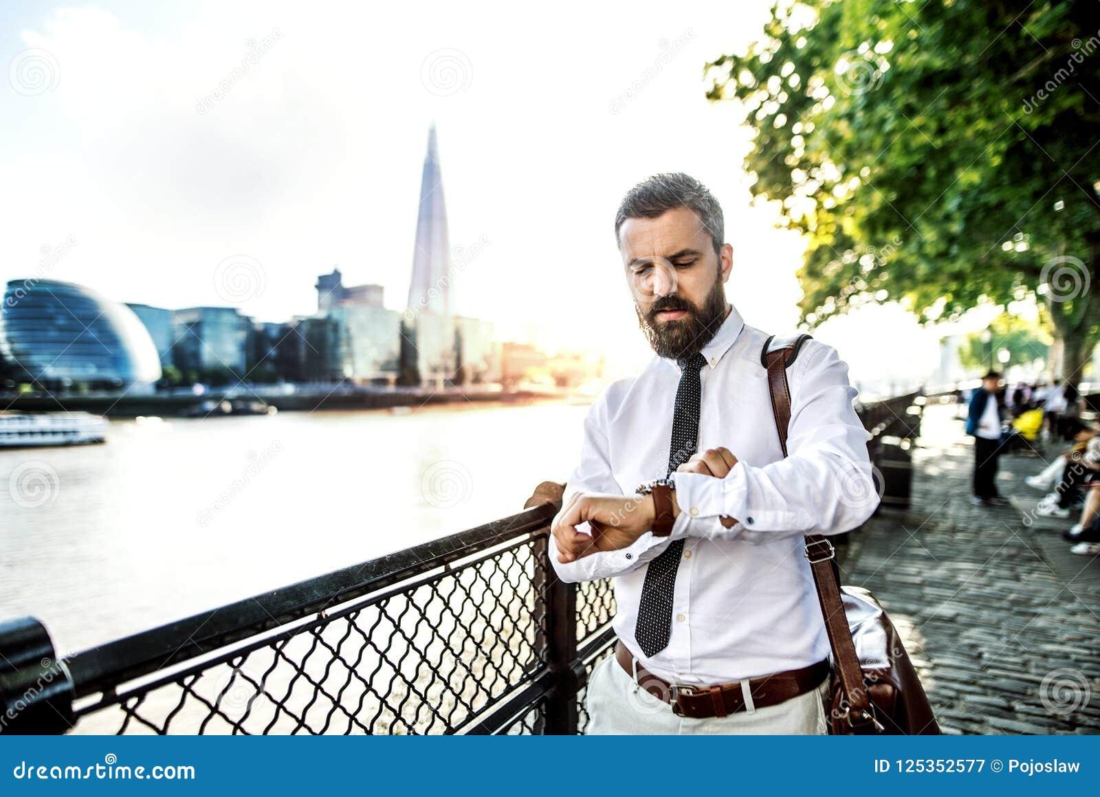 Modnisia biznesmen z laptop torby odprowadzeniem rzeką w Londyn, sprawdza czas