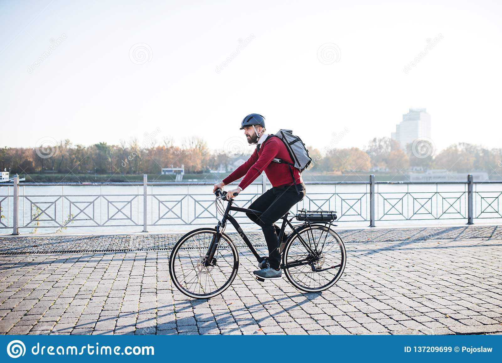 Modnisia biznesmena dojeżdżający z elektryczny rowerowy podróżować pracować w mieście