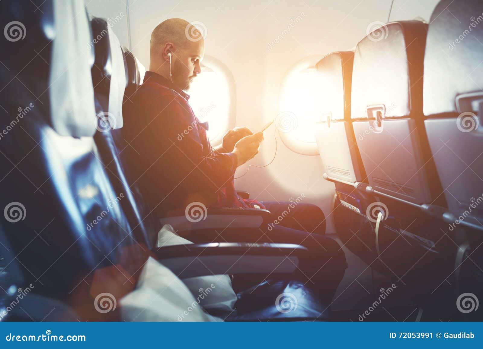 Modnisia facet słucha muzyka w hełmofonach przez komórka telefonu