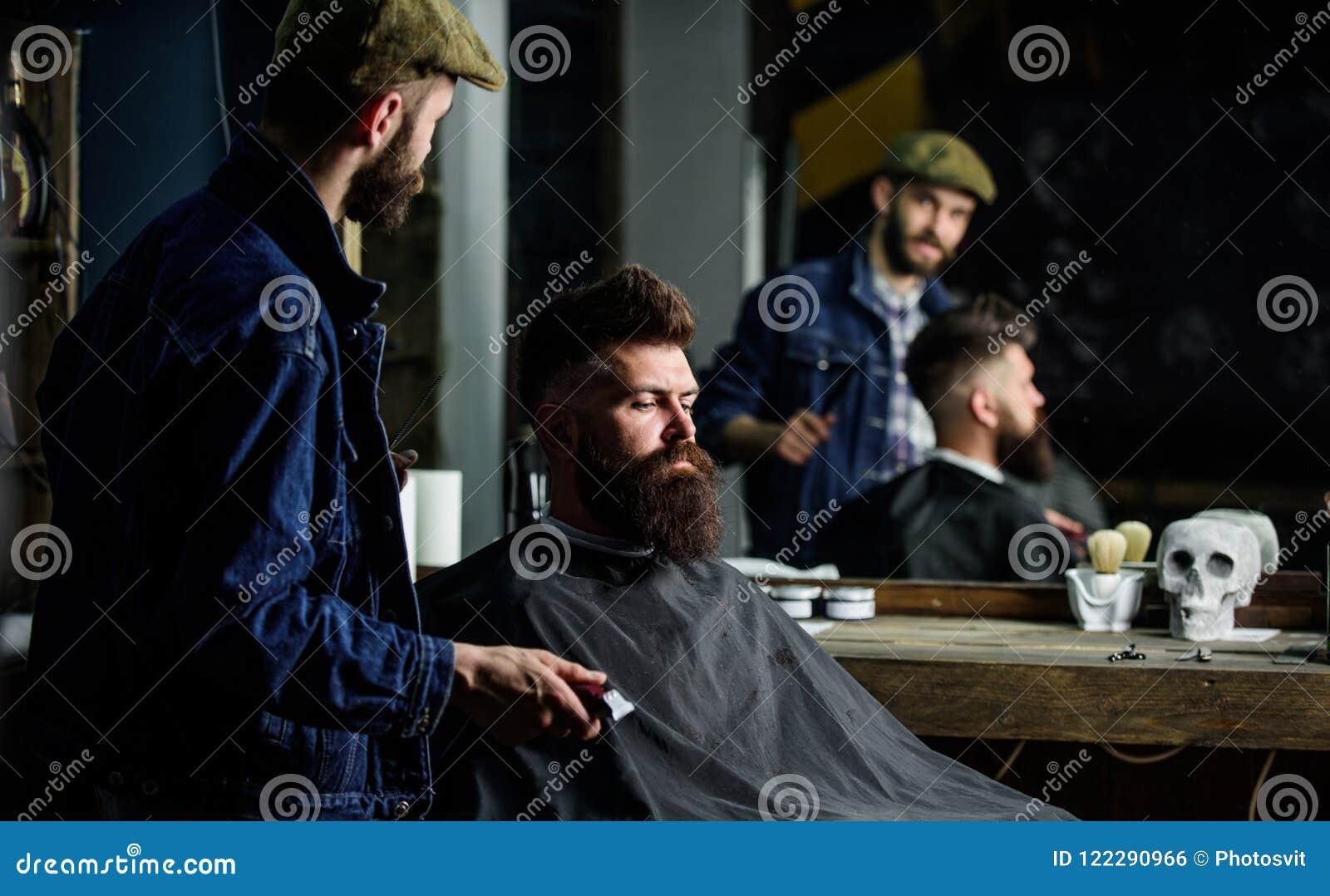 Modnisia klient dostać nowego ostrzyżenie Fryzjer męski z włosianym cążki patrzeje lustro, zakładu fryzjerskiego tło Profesjonali