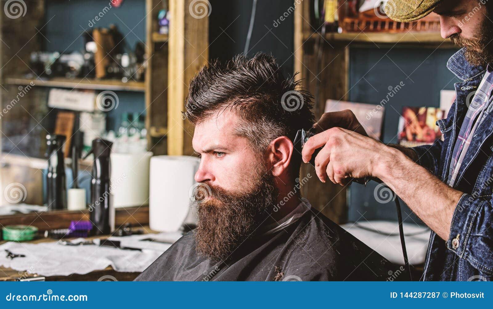 Modnisia klient dostaje ostrzyżenie Ostrzyżenia pojęcie Fryzjera męskiego tytułowania włosy brodaty klient z gręplą i cążki barbe