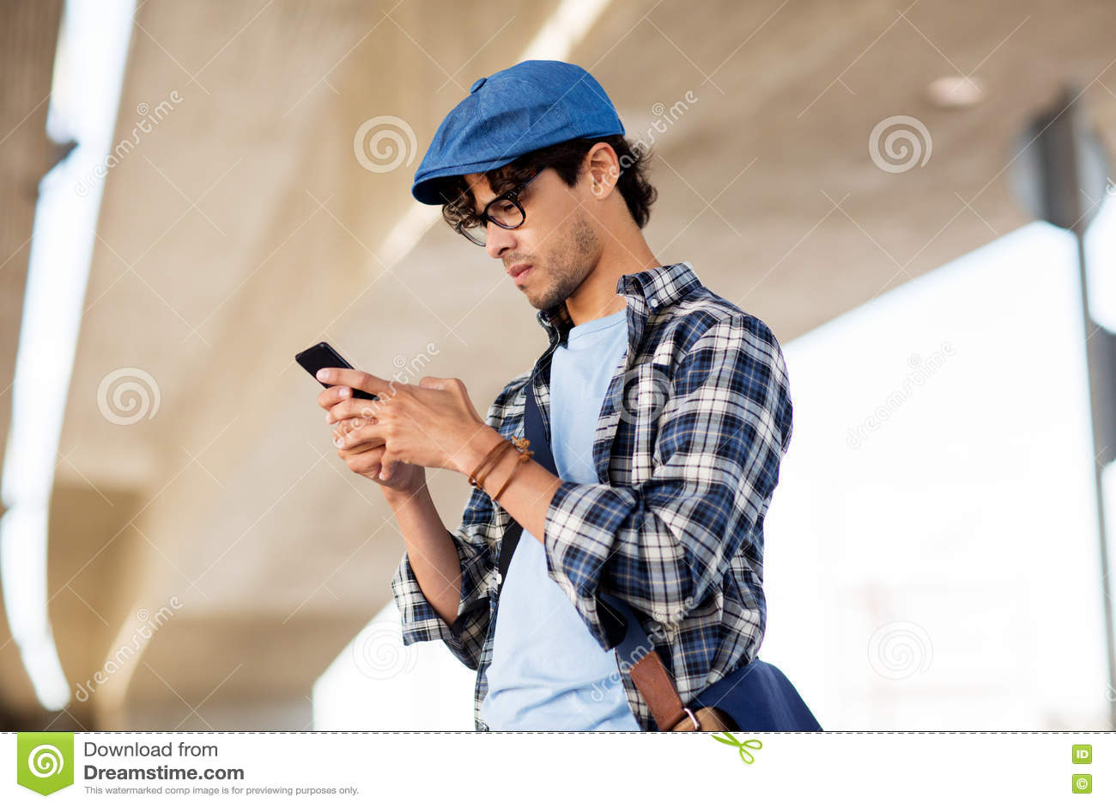 Modnisia mężczyzna texting wiadomość na smartphone