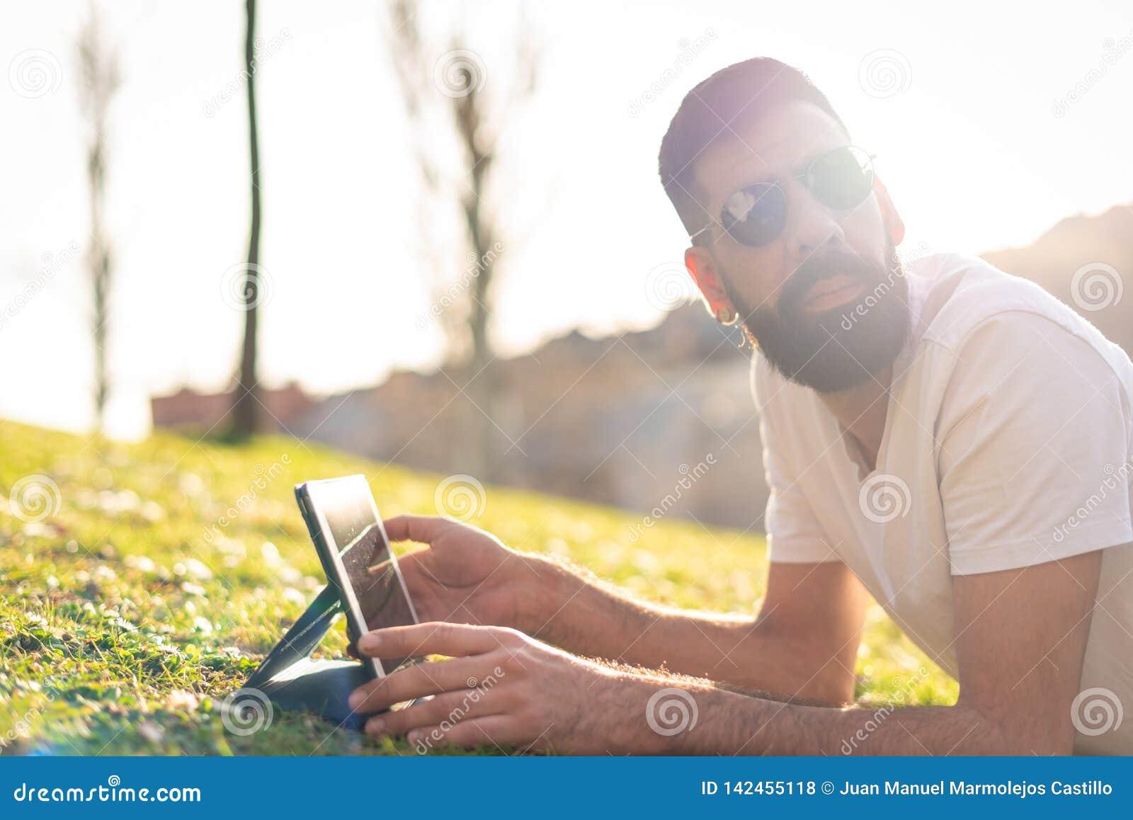 Modnisia mężczyzna Używa cyfrową pastylkę w parku
