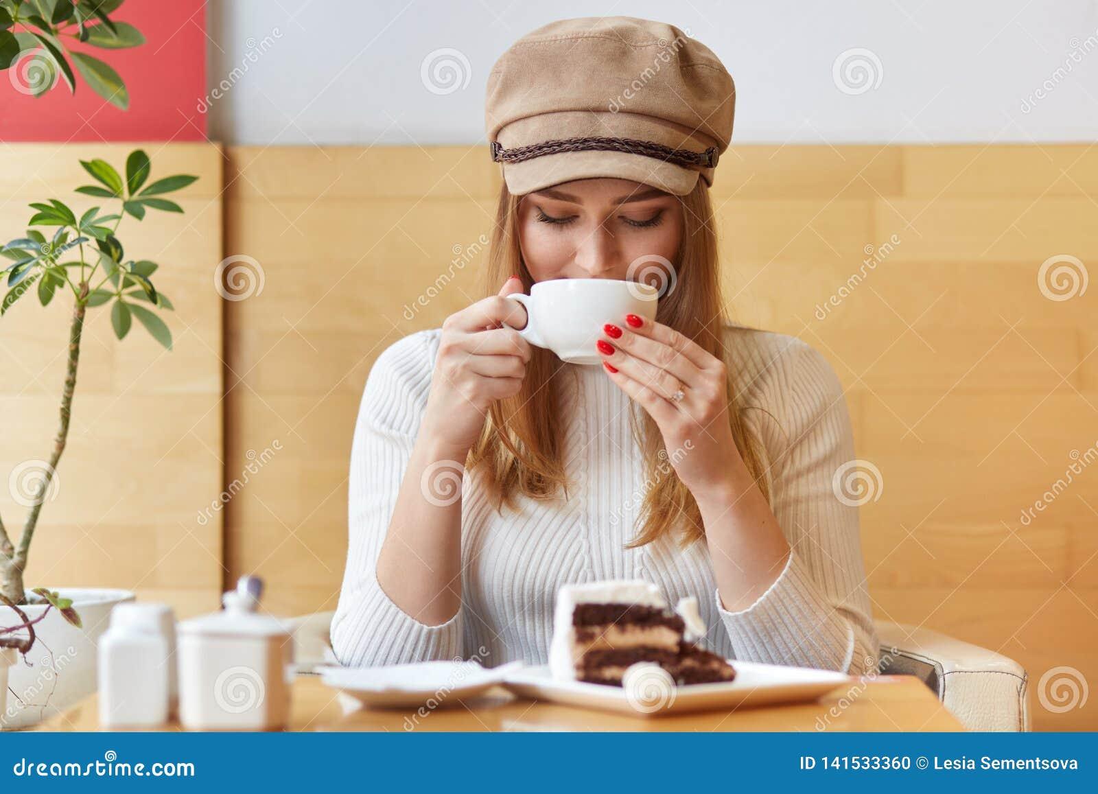 Modny młody piękny żeński projektant przerwę po pracy, odwiedza lokalnego bufet, pije gorącego napój, trzyma białego kubek,