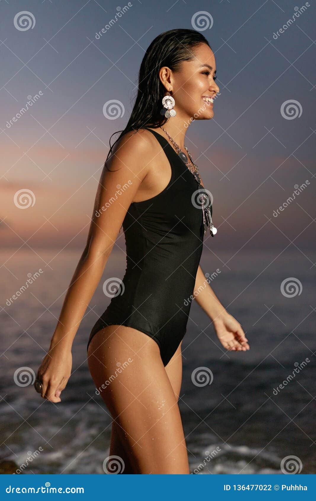 Modo della donna Ragazza alla moda in costume da bagno alla costa di mare al tramonto