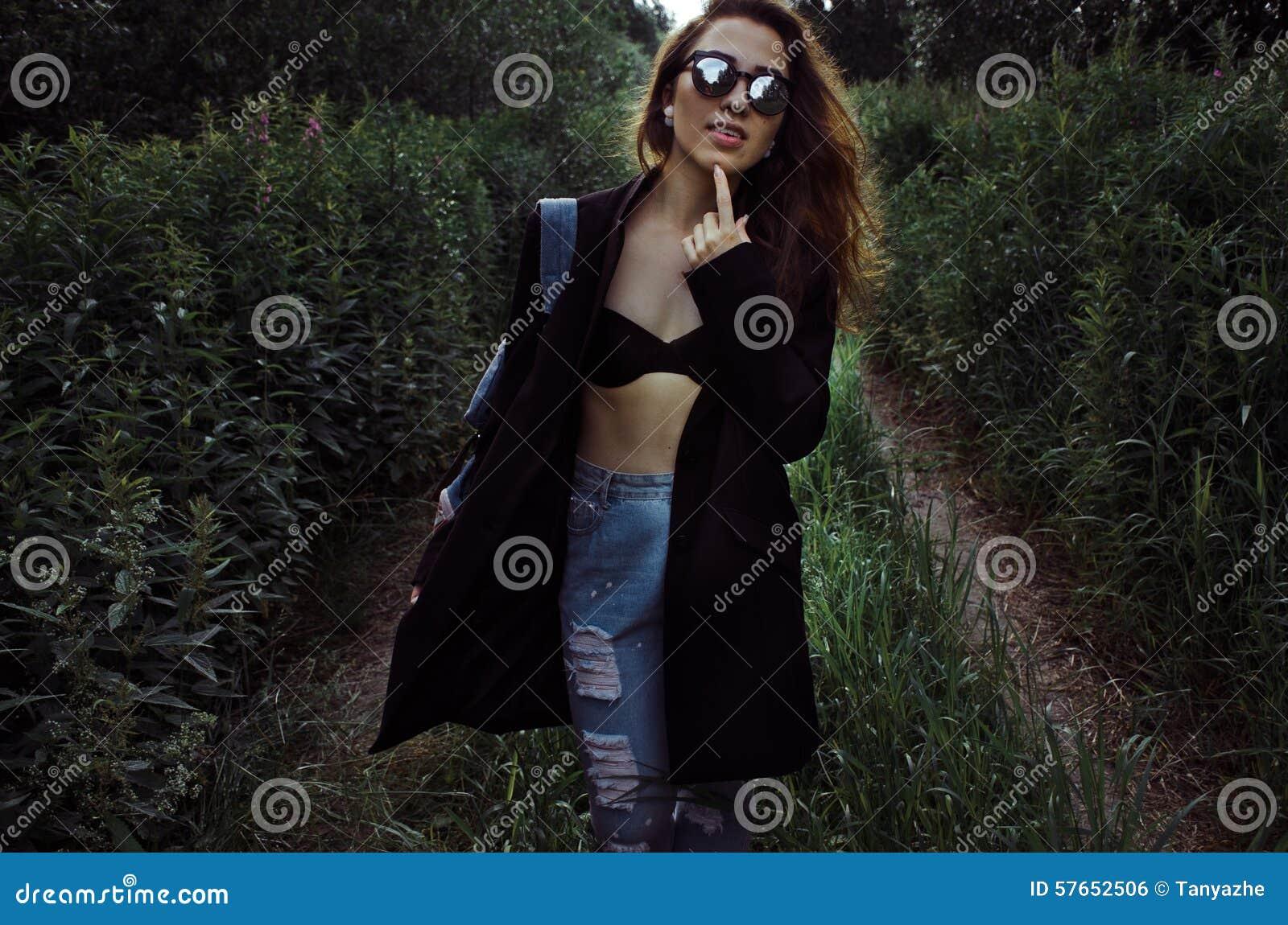 Mody dziewczyna w czarnym żakiecie rusza się wzdłuż lasowej drogi