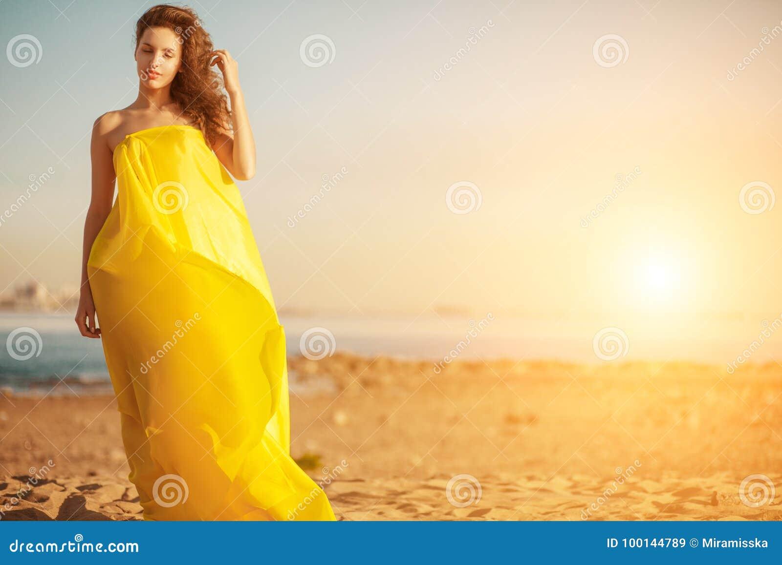 Mody dziewczyna w długiej sukni przeciw lato zmierzchu tłu