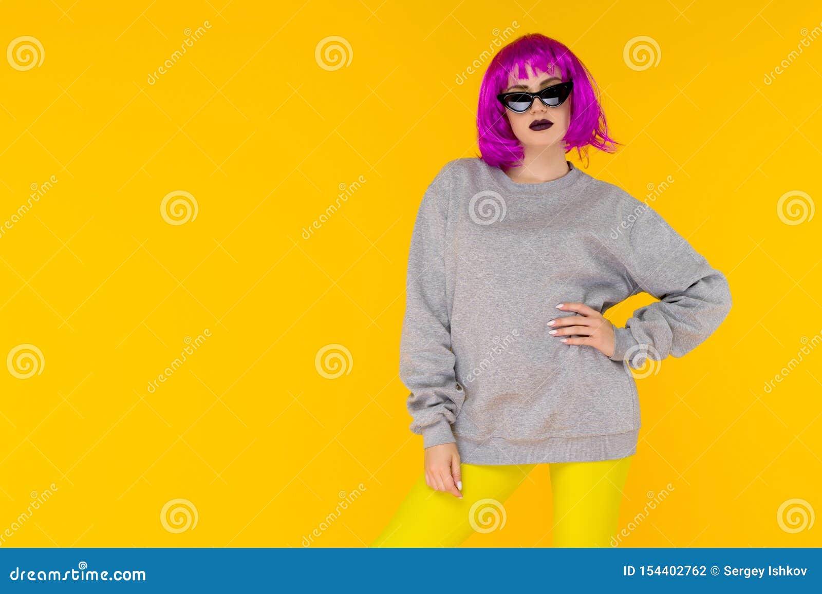 Mody dziewczyny portret na żółtym tle Szalona stylowa młoda kobieta w różowej peruce