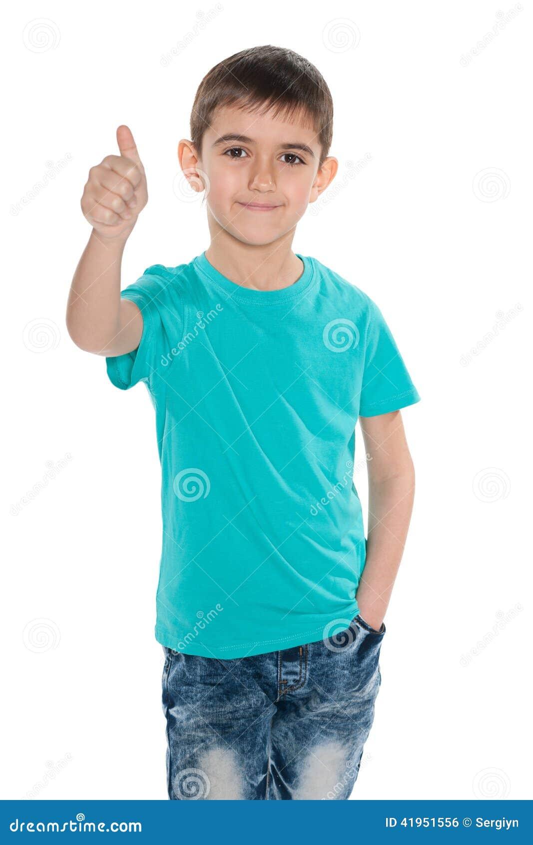 Mody młoda chłopiec trzyma jego kciuk up