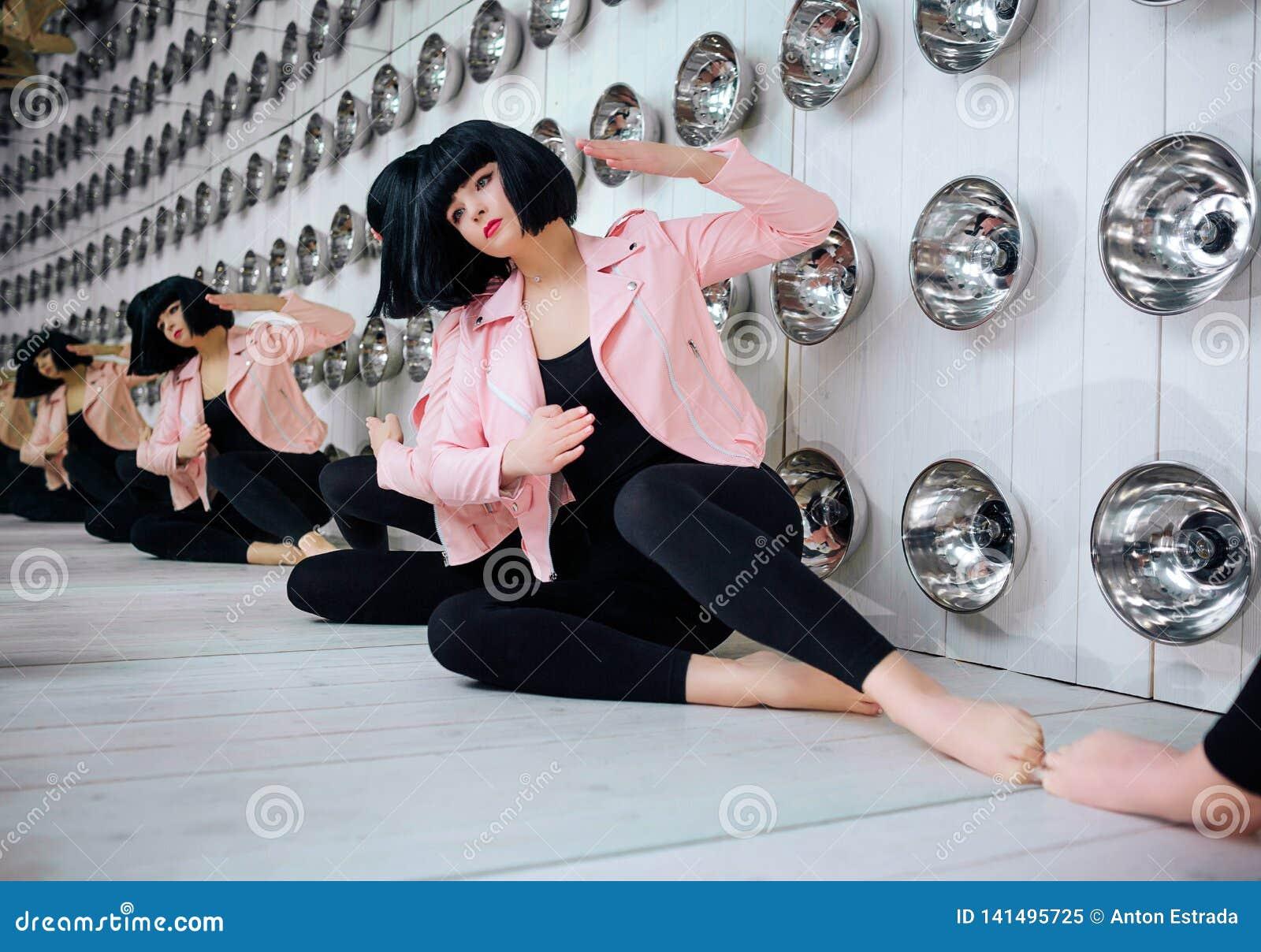 Mody pokraka Splendor syntetyczna dziewczyna, sfałszowana lala z pustym spojrzeniem i krótki czarni włosy, siedzimy w studiu eleg