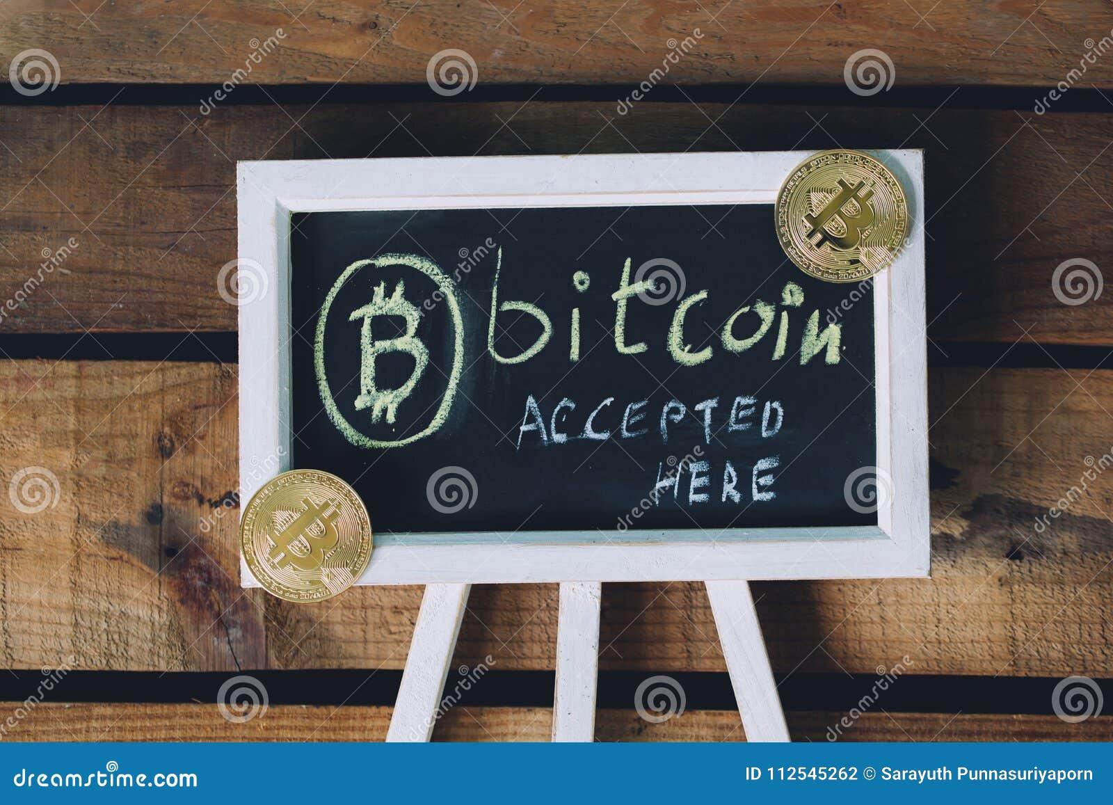 A moeda cVirtual virtual Bitcoin aceitou assina aqui sobre o fundo de madeira com bitcoins reais no canto