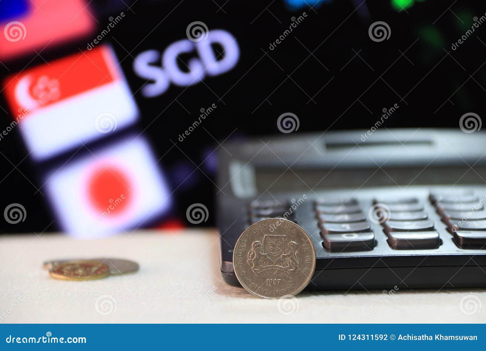 Moeda de Singapura de vinte centavos no SGD do anverso com calculadora preta e placa digital do dinheiro da troca de moeda