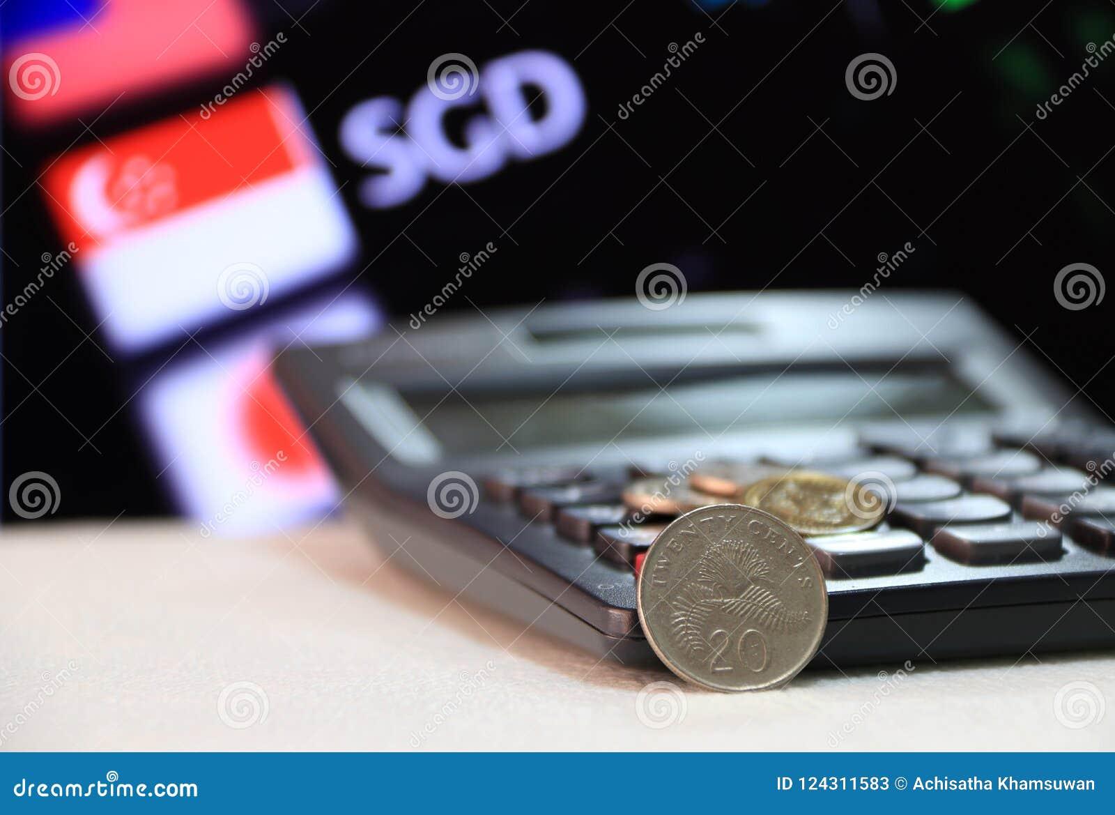 Moeda de Singapura de vinte centavos no SGD reverso com calculadora preta e placa digital do fundo do dinheiro da troca de moeda