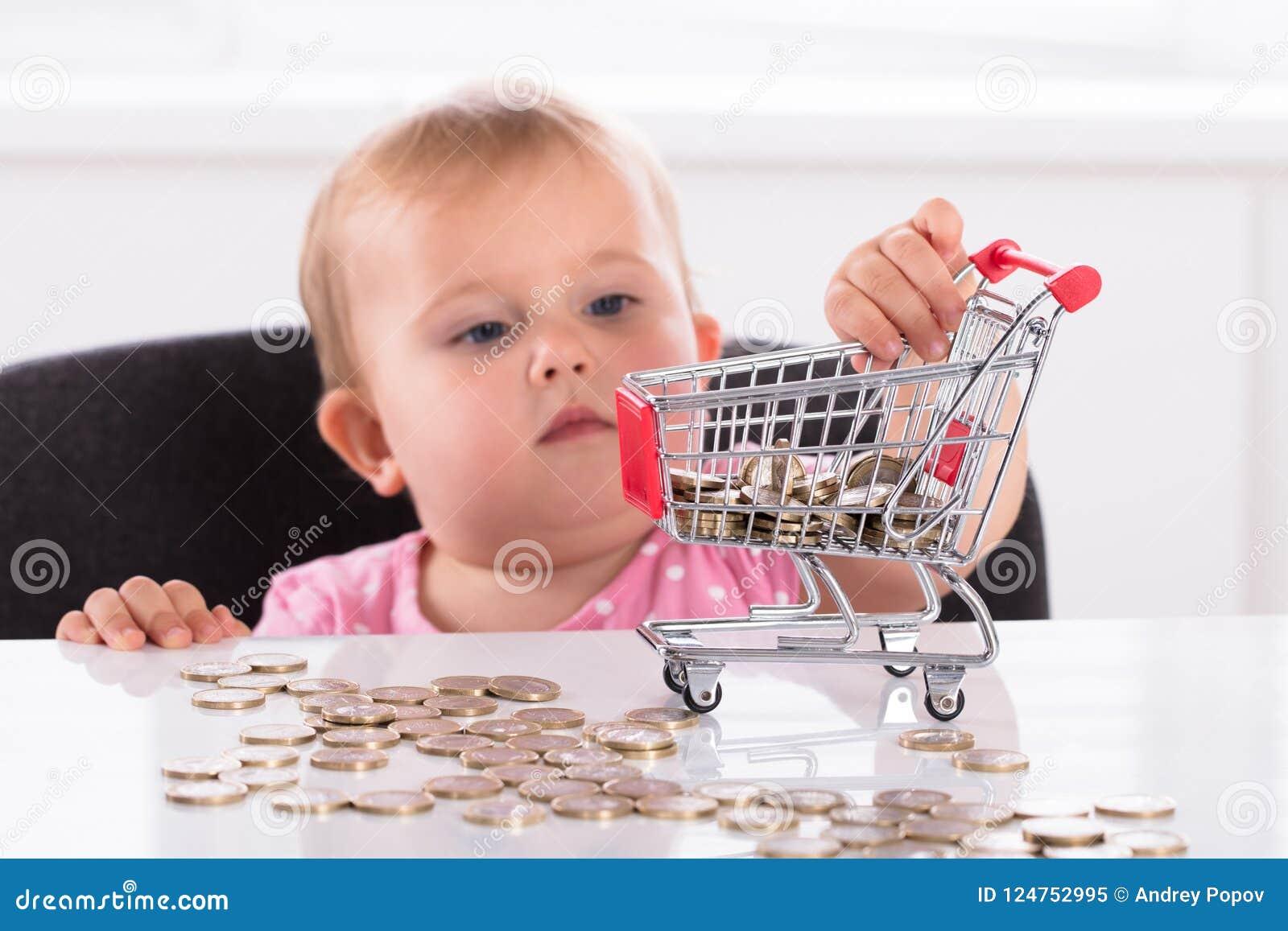 Moeda levando do bebê no trole da compra
