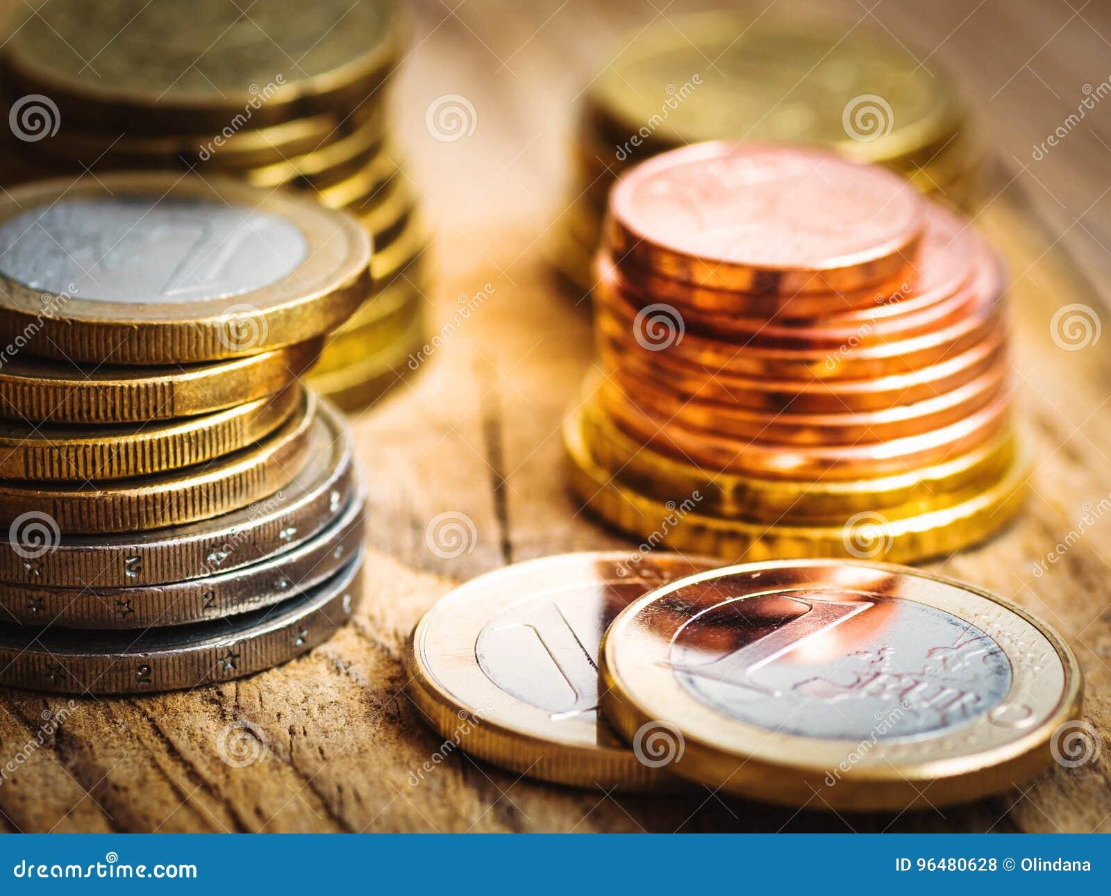 Moedas brancas e douradas brilhantes empilhadas do valor diferente no fundo de madeira, finanças do Euro, investimento, estoque,